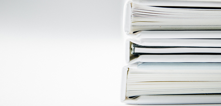 stack of white binders and documents to illustrate food safety management systems