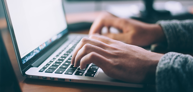 hands typing on laptop to illustrate food safety training