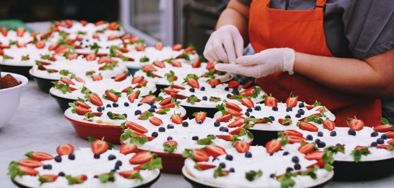 person preparing fruit cakes to illustrate food safety