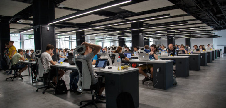 office space with lots of people working on desks with computers