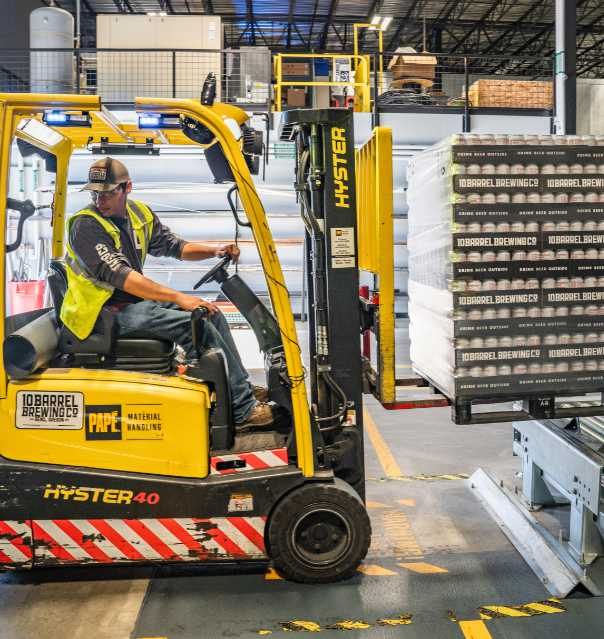 person driving forklift in warehouse to illustrate brcgs standards