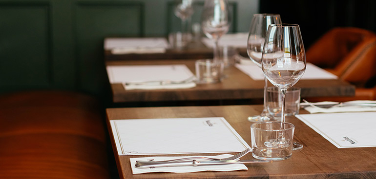 restaurant tables with placemats and cuttlery